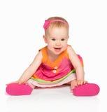 Glückliches kleines Baby in hellem mehrfarbigem festlichem Kleiderisolator Stockfoto