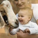 Glückliches kleines Babylachen glücklich beim Sitzen auf den Händen der Mutter zu lizenzfreie stockbilder