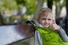 Glückliches kleines blondes Jungenshow-O.K.zeichen, das auf einer Bank sitzt Stockbilder
