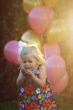 Glückliches kleines blondes kaukasisches Mädchen draußen mit Ballonen Stockfotografie