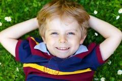 Glückliches kleines blondes Kind, Kinderjunge mit den blauen Augen, die auf das Gras mit Gänseblümchen legen, blüht im Park Stockbild