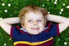 Glückliches kleines blondes Kind, Kinderjunge mit den blauen Augen, die auf das Gras mit Gänseblümchen legen, blüht im Park Lizenzfreies Stockbild