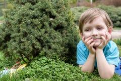 Glückliches kleines blondes Kind mit den blauen Augen, die auf den Grasbäumen im Park legen oder stehen Lizenzfreie Stockbilder