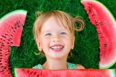 Glückliches kleines blondes Mädchen, das auf dem Gras mit großer Scheibenwassermelone in der Sommerzeit liegt Lächeln Beschneidun Stockfoto