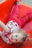 Glückliches kleines blondes Mädchen, das auf rotem Plastikspielplatzdia liegt und Kamera betrachtet Stockbild