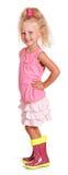 Glückliches kleines blondes Mädchen in den Blusenrock-Gummistiefeln lokalisiert Lizenzfreie Stockbilder