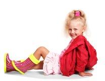 Glückliches kleines blondes Mädchen in der Jacke, Gummistiefel, Rock lokalisiert Stockbild