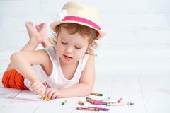 Glückliches kleines Künstlermädchen in einem Hut zeichnet Bleistift Stockfotografie