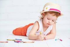 Glückliches kleines Künstlermädchen in einem Hut zeichnet Bleistift Stockbilder