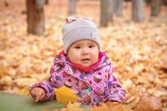 Glückliches kleines Kind, Baby, das im Herbst spielt stockbild