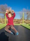 Glückliches kleines Kind, das auf Trampoline springt Lizenzfreie Stockfotos
