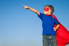 Glückliches kleines Kind, das Superhelden spielt lizenzfreies stockfoto