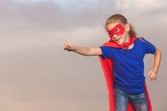 Glückliches kleines Kind, das Superhelden spielt stockfoto