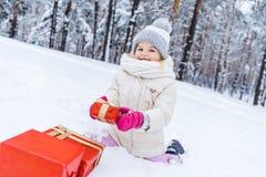 glückliches kleines Kind in der Winterkleidung, die auf Schnee mit Geschenkboxen und dem Lächeln sitzt stockfoto