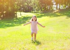 Glückliches kleines Kind des sonnigen Fotos, das Sommertag genießt Stockbild