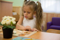 Glückliches kleines Kind, entzückendes blondes Kleinkindmädchen, den Spaß habend, der zusammen mit zusammenbauenden Stücken des P Stockfoto