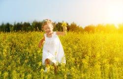 Glückliches kleines Kindermädchen, das auf Feld mit gelben Blumen läuft Stockfoto