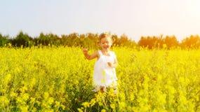 Glückliches kleines Kindermädchen, das auf Feld mit gelben Blumen läuft Lizenzfreie Stockbilder