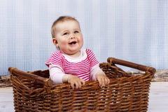 Glückliches kleines Kleinkind, das im Korb lacht Lizenzfreie Stockbilder