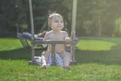 Glückliches kleines lächelndes Kind, das auf einem Schwingen im Sommer im Freien schwingt stockbild