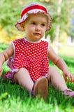 Glückliches kleines Mädchen auf einem Rasen Lizenzfreie Stockfotos