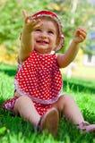 Glückliches kleines Mädchen auf einem Rasen Stockbilder