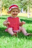 Glückliches kleines Mädchen auf einem Rasen Stockfoto