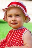 Glückliches kleines Mädchen auf einem Rasen Stockfotografie