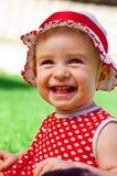 Glückliches kleines Mädchen auf einem Rasen Stockbild