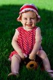 Glückliches kleines Mädchen auf einem Rasen Lizenzfreies Stockfoto