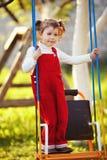 Glückliches kleines Mädchen auf Schwingen Stockbilder