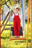 Glückliches kleines Mädchen auf Schwingen Lizenzfreie Stockfotos