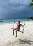 Glückliches kleines Mädchen auf Schwingen am Strand lizenzfreies stockfoto