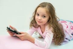 Glückliches kleines Mädchen, das auf Bett mit Tablet-Computer liegt Lizenzfreie Stockbilder