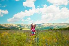 Glückliches kleines Mädchen, das auf das Feld springt lizenzfreie stockfotos