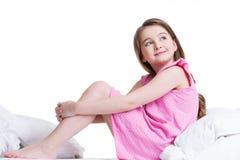 Glückliches kleines Mädchen, das auf dem Bett sitzt und oben schaut. Lizenzfreie Stockfotografie
