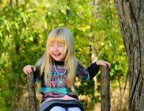 Glückliches kleines Mädchen, das auf dem Bretterzaun sitzt lizenzfreie stockfotos