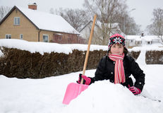 Glückliches kleines Mädchen, das auf dem Schnee sitzt Stockbilder