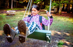 Glückliches kleines Mädchen, das auf dem Schwingen schwingt Lizenzfreies Stockfoto