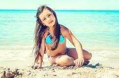 Glückliches kleines Mädchen, das auf den Strand springt Lizenzfreies Stockbild