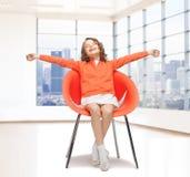 Glückliches kleines Mädchen, das auf Designerstuhl sitzt Stockfotografie