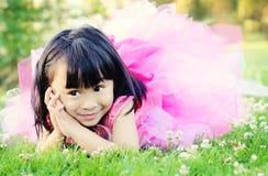 Glückliches kleines Mädchen, das auf Gras in einem Park legt Lizenzfreies Stockfoto