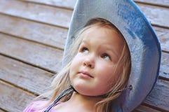Glückliches kleines Mädchen, das auf hölzernem Hintergrund aufwirft Stockfotografie