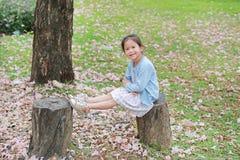 Glückliches kleines Mädchen, das auf hölzernen Klotz gegen fallende rosa Blume im Sommergarten sitzt lizenzfreies stockfoto