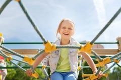 Glückliches kleines Mädchen, das auf Kinderspielplatz klettert Stockfoto
