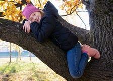 Glückliches kleines Mädchen, das auf Niederlassung von großem sitzt und am sonnigen Herbsttag lächelt stockfotos