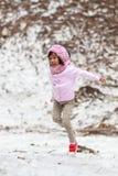 Glückliches kleines Mädchen, das auf Schnee springt Lizenzfreies Stockfoto