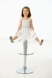 Glückliches kleines Mädchen, das auf Stuhl sitzt Stockfotos