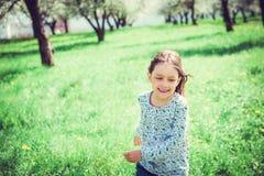 Glückliches kleines Mädchen, das in den Garten läuft Stockbild