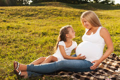 Glückliches kleines Mädchen, das den schwangeren Bauch ihrer Mutter umarmt stockfotos
